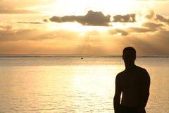 Silhueta de um homem que presta atenção ao por do sol Imagens de Stock Royalty Free