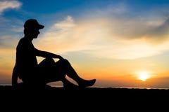 Silhueta de um homem que senta-se perto do oceano Fotos de Stock Royalty Free