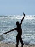 Silhueta de um menino do Afro na praia Imagem de Stock