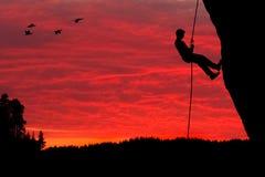Silhueta Rappelling do montanhista de rocha Imagem de Stock Royalty Free