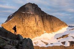 Silhueta de um montanhista na frente de uma parede da montanha foto de stock royalty free
