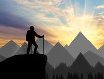 A silhueta de um montanhista na parte superior olha na distância sobre as montanhas Fotografia de Stock