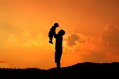 Silhueta de um pai e de um filho que jogam fora no por do sol fotografia de stock