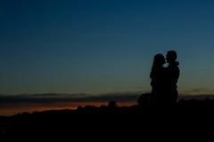Silhueta de um par com um por do sol bonito fotos de stock royalty free