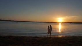Silhueta de um par no amor em um fundo tropical do por do sol vídeos de arquivo