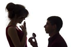 A silhueta de um par novo, de uma posição do homem em joelhos e de fazer uma proposta à menina, o indivíduo dá o anel e quê-lo ob imagens de stock