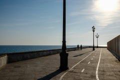 Silhueta de um par que anda ao longo de um passeio do beira-mar no por do sol Imagem de Stock Royalty Free
