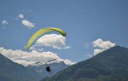 Silhueta de um paraglider e de montanhas imagem de stock