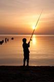 Silhueta de um pescador do menino Fotos de Stock