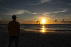 Silhueta de um por do sol de observação do homem sobre o oceano fotografia de stock royalty free