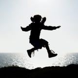 Silhueta de um salto da menina Fotografia de Stock