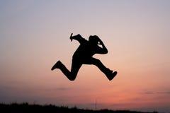 Silhueta de um salto do homem Fotografia de Stock