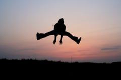 Silhueta de um salto do homem Fotos de Stock