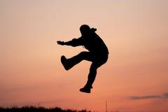 Silhueta de um salto do homem Fotografia de Stock Royalty Free