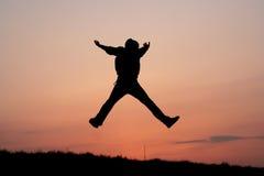 Silhueta de um salto do homem Foto de Stock