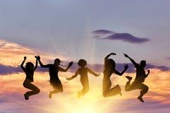 Silhueta de um salto feliz do grupo de pessoas fotografia de stock