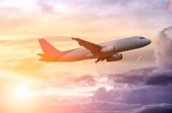 Silhueta de um voo plano no por do sol bonito imagem de stock