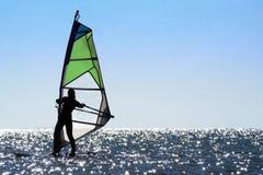 Silhueta de um windsurfer da mulher fotografia de stock