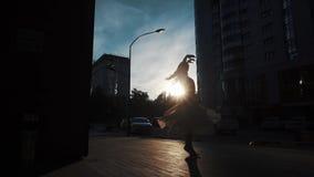 Silhueta de uma bailarina em um vestido de voo que dança fora dança magro da menina no fundo de construções urbanas filme