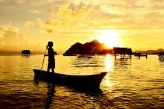 Silhueta de uma criança que rema em um barco Fotografia de Stock