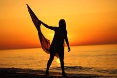 Silhueta de uma dança da menina com uma bandeira Imagens de Stock