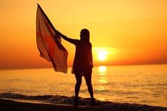 Silhueta de uma dança da senhora com uma bandeira Foto de Stock