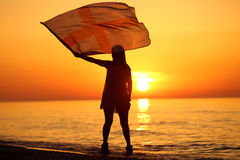 Silhueta de uma dança da senhora com uma bandeira Fotografia de Stock