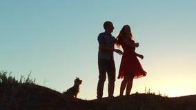 Silhueta de uma dança lenta nova feliz do casal e do cão fora no por do sol vídeo de movimento lento Homem e menina vídeos de arquivo