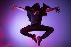 A silhueta de uma dança masculina do dançarino da ruptura do hip-hop no fundo colorido imagens de stock