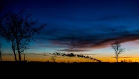 Silhueta de uma exploração agrícola de vento e de um por do sol foto de stock