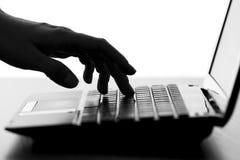 A silhueta de uma fêmea entrega a datilografia no teclado do netbook foto de stock