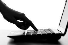 A silhueta de uma fêmea entrega a datilografia no teclado do netbook Imagem de Stock