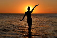 Silhueta de uma figura fêmea misteriosa no fundo do por do sol do mar fotos de stock