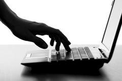 A silhueta de uma fêmea entrega a datilografia no teclado do netbook Fotografia de Stock