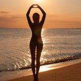 Silhueta de uma ioga praticando da jovem mulher no beira-mar no por do sol fotografia de stock
