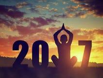 Silhueta de uma ioga praticando da menina no ano novo Imagens de Stock Royalty Free