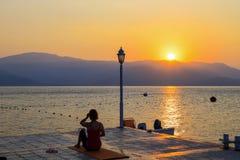 Silhueta de uma jovem mulher que execute exercícios da ioga em uma manhã do verão no litoral no nascer do sol Esportes, estilo de fotos de stock