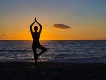 Silhueta de uma jovem mulher que faz a ioga na praia no por do sol fotografia de stock royalty free