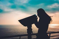 Silhueta de uma jovem mulher que olha através dos binóculos, Lima, Pe imagem de stock