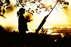 Silhueta de uma jovem mulher que tira uma imagem em uma armação na natureza, na posição fêmea sob a árvore com escova e na paleta imagem de stock