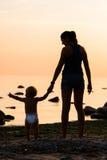 Silhueta de uma mãe e de seu bebê na praia Imagens de Stock