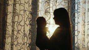 Silhueta de uma mãe nova que joga com o bebê pela janela no por do sol filme