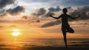 Silhueta de uma meditação da ioga da jovem mulher durante um por do sol surpreendente Fotografia de Stock Royalty Free