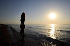 Silhueta de uma menina contra o por do sol pelo mar Imagens de Stock Royalty Free