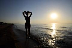 Silhueta de uma menina contra o por do sol pelo mar Fotografia de Stock Royalty Free