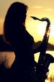 Silhueta de uma menina em um vestido com um instrumento musical de bronze em suas mãos que olham pensativamente na distância imagens de stock