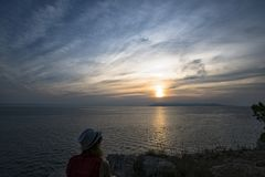 Silhueta de uma menina no fundo do por do sol sobre o mar de adriático fotos de stock
