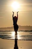 Silhueta de uma menina no fundo do sol fotos de stock