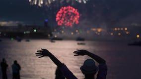Silhueta de uma menina no fundo dos fogos-de-artifício a mulher levanta felizmente seus mãos e divertimento ter no feriado filme