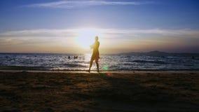 Silhueta de uma menina no por do sol, na perspectiva do mar, golpe ginásticos fazendo engraçados da menina pernudo delgada no video estoque